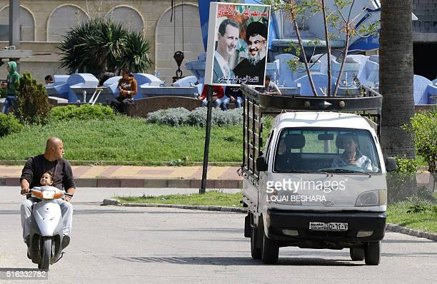 A poster with portraits of Syrian President Bashar alAssad and Lebanon's Hezbollah chief Hassan Nasrallah is seen in the coastal city of Latakia the...