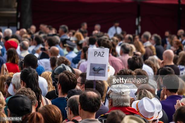 A poster with the text Peace and the image of a dove is seen during the event Barcelona celebrated the first anniversary of the terrorist attack on...