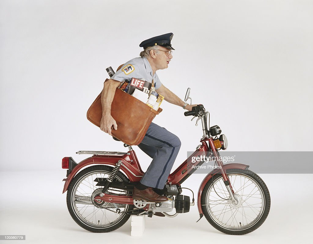 Poster worker delivering magazine on motorbike : Stock Photo