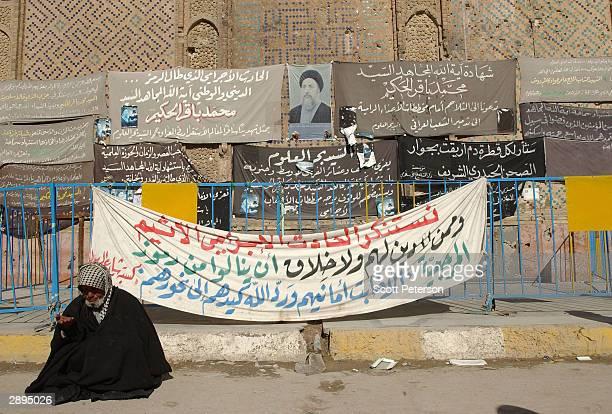 Posters adorn the scarred wall of the Imam Ali shrine on January 21 2004 to mark the place where respected Ayatollah Mohamed Bakr alHakkim the leader...