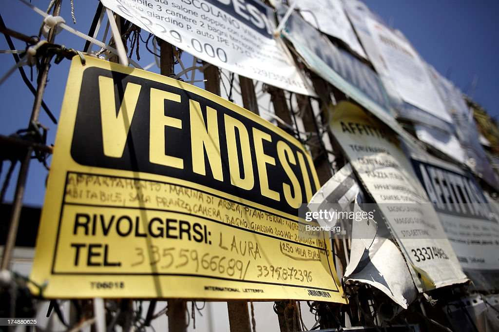 Posters advertising properties 'For Sale' and 'To Rent' hang on a fence in Torvaianica, near Rome, Italy, on Saturday, July 27, 2013. Italy's home prices are low enough to trigger an increase in purchases for the first time since 2006, though that won't lift values for at least two years, according to the Nomisma institute. Photographer: Alessia Pierdomenico/Bloomberg via Getty Images