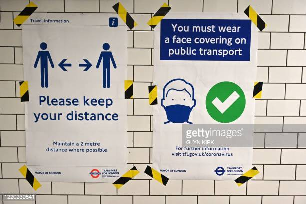 Posters advise people on social distancing and the wearing of face coverings on the underground network, at Notting Hill tube station in London, on...