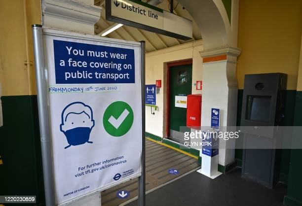 Posters advise people on the wearing of face coverings on the underground network at Wimbledon Park tube station in London on June 15 2020 after new...
