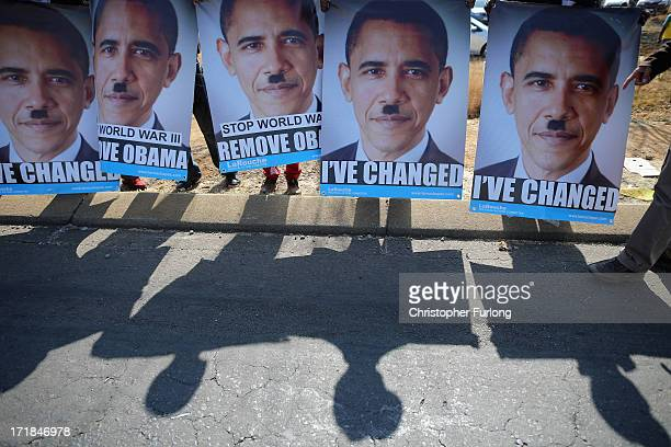 Posters depicting a likeness of Barack Obama are held by protesters outside Johannesburg University in Soweto in advance of President Obama's meeting...