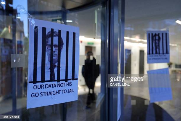 Posters depicting Cambridge Analytica's CEO Alexander Nix behind bars with the slogan 'Our Data Not His Go Straight To Jail' are pictured at the...
