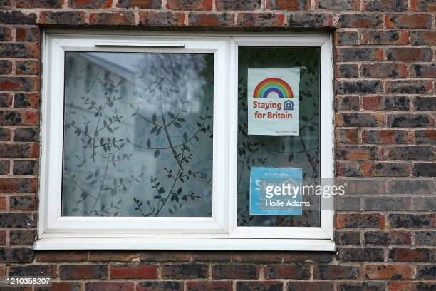 Posters encouraging people to stay inside are displayed in an apartment window on April 18, 2020 in London, England. In a press conference on...