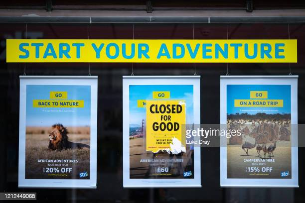 Posters from Extinction Rebellion are stuck to the window of a travel agent, asking the Government to stop handouts to destructive big businesses as...