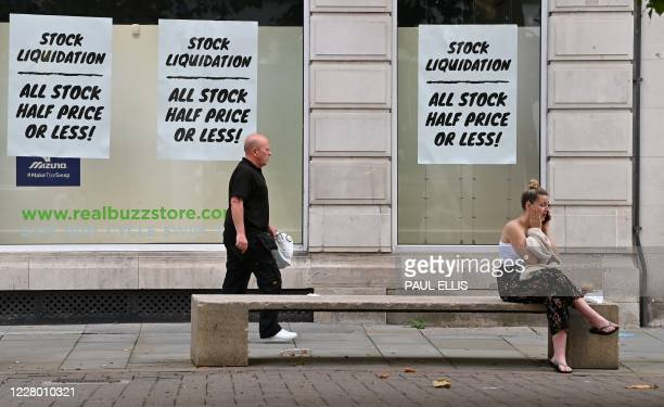 """Posters in the window a a closing-down shop advertise a """"Stock Liquidation"""" in Manchester, northern England on August 12, 2020. - Britain's economy..."""
