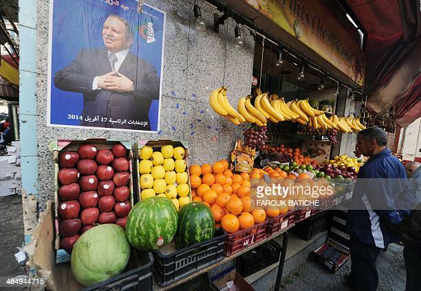 Posters of Algerian president Abdelaziz Bouteflika and candidate in the upcoming presidential elections are seen next to a vegetable vendor in the...