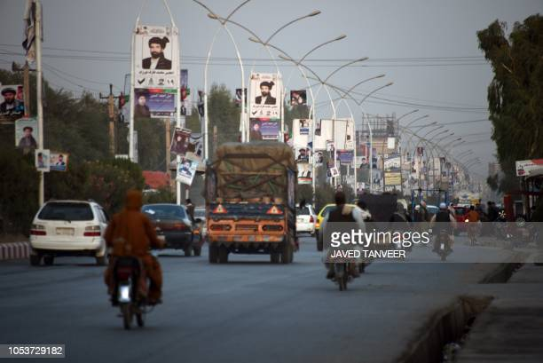 Posters of candidates are pictured along a road ahead of legislative election in Kandahar province on October 26 2018 Afghans will risk their lives...