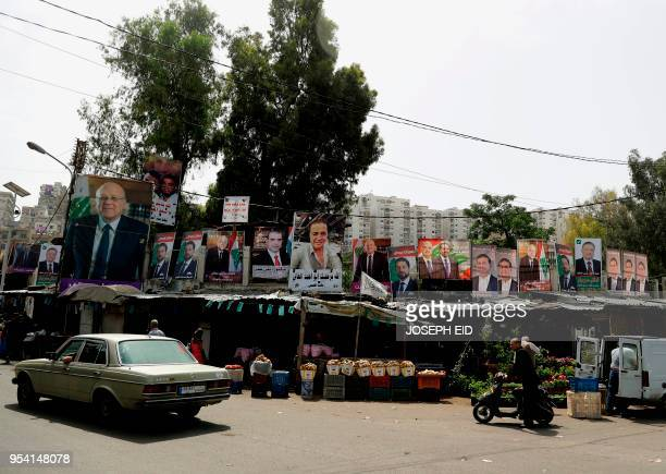 Posters of candidates for the upcoming Lebanese parliamentary elections hang above fresh produce stalls in the northern Lebanese city Tripoli's Bab...