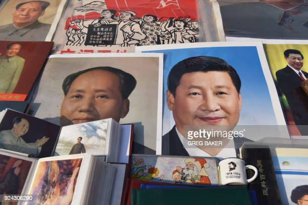 Posters of Chinese President Xi Jinping and late communist leader Mao Zedong are seen at a market in Beijing on February 26, 2018. Xi Jinping's...