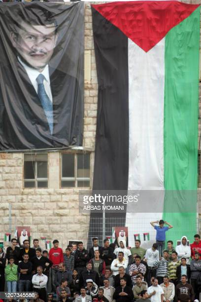 Posters of Jordanian King Abdullah II and the Palestinian national flag hang during a friendly football match between the Palestinian team and Jordan...
