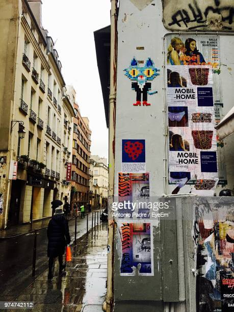 Posters On Wall By Woman Walking On Wet Footpath