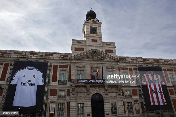 Posters representing the jerseys of the Real Madrid and Atletico de Madrid football clubs hang on the facade of the Royal Post Office and the current...