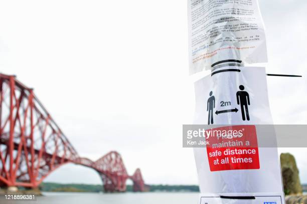 Posters with Covid-19 regulations and advice on a road sign at the Town Pier with the Forth Bridge in the background, after the the Scottish...
