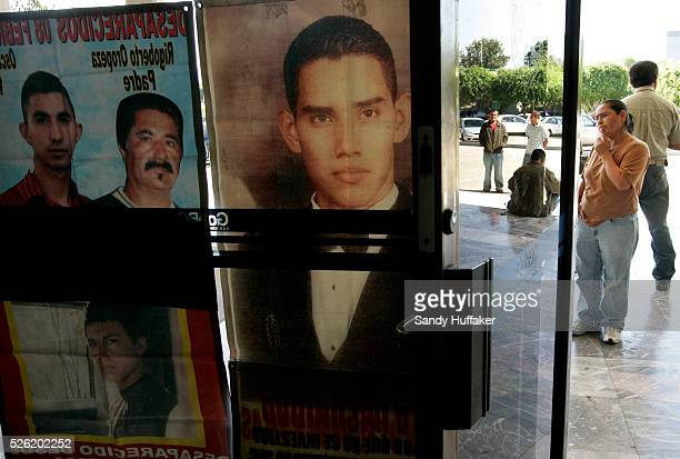 Posters with images of missing and murdered persons hang on a window outside of Tijuana City Hall on Friday October 9 2009 in Mexico For many family...
