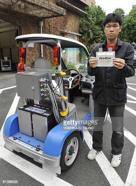A postgraduated student of Tokyo University poses holding a unit of the electric capacitor from the electric vehicle 'CCOMS' at the universary campus...