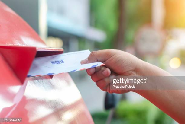 posting a letter to red british postbox on street - sending stock pictures, royalty-free photos & images