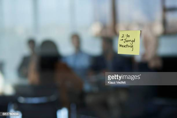 Postit note on glass wall of conference room