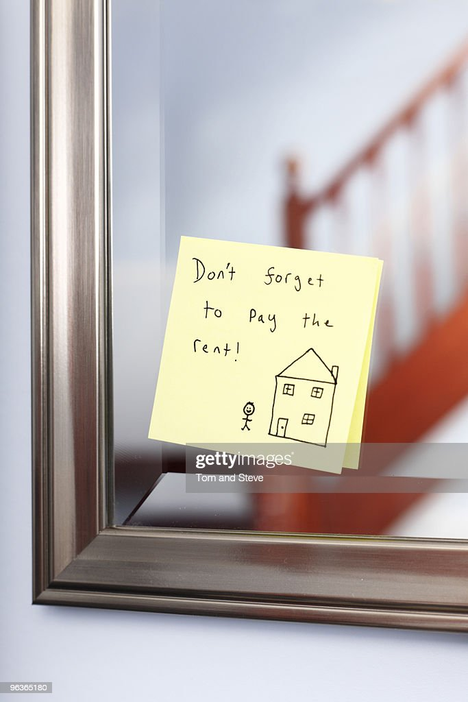Post-it note with rent reminder on mirror : Stock Photo