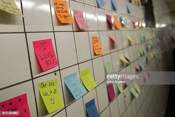 Postit notes many with politically themed messages hang on a wall at the 6th Avenue subway station as part of a public art project entitled 'Subway...