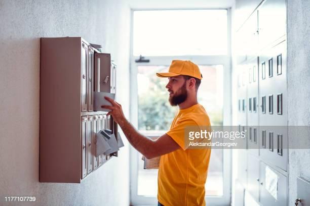 postman delivering bills in apartment building mailbox - carteiro imagens e fotografias de stock