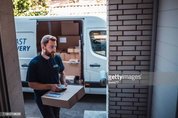postman delivery a package to a customer. - delivery person stock pictures, royalty-free photos & images