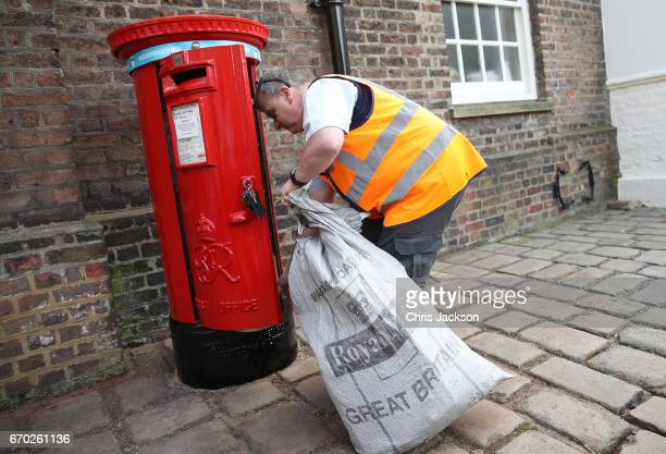 A postman empties the Kensington Palace postbox with the Heads Together headband on it placed there by Catherine Duchess of Cambridge in support of...