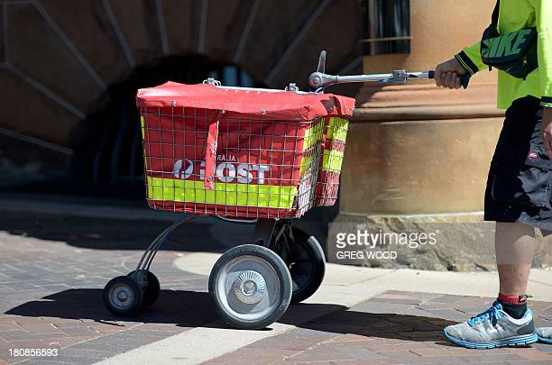 A postman from Australia Post makes postal deliveries in Sydney's central business district in this photo taken on September 12 2013 AFP PHOTO / Greg...