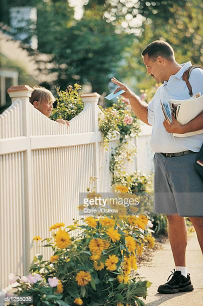 postman giving a girl her mail standing by a picket fence in summer - postal worker stock pictures, royalty-free photos & images
