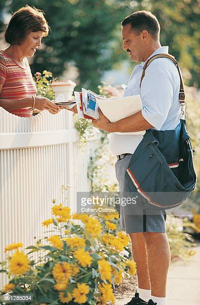 Postman Giving a Woman Her Mail Standing By a Picket Fence in Summer