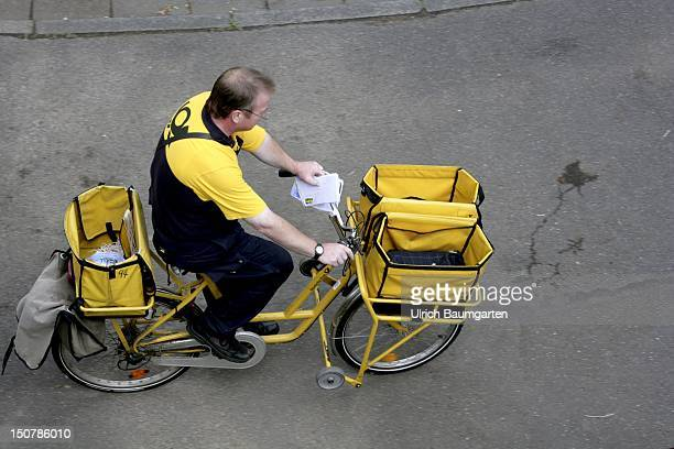 Postman of the Deutsche Post AG on bicycle