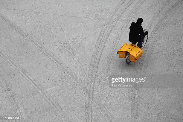 Postman on a bicycle, delivers mail early in the morning despite the snowy weather in Groningen, The Netherlands