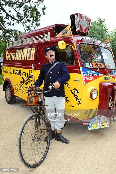 A postman performer poses in front of an accordeonist Yvette Horner bus on July 9 2010 prior to the start of the 2275 km and 6th stage of the 2010...