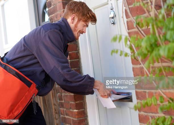 Postman posting letters through resident's door