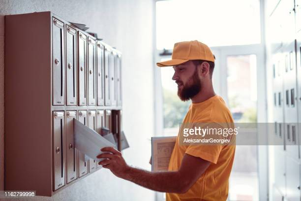 postman putting letter in mailbox - correspondence stock pictures, royalty-free photos & images