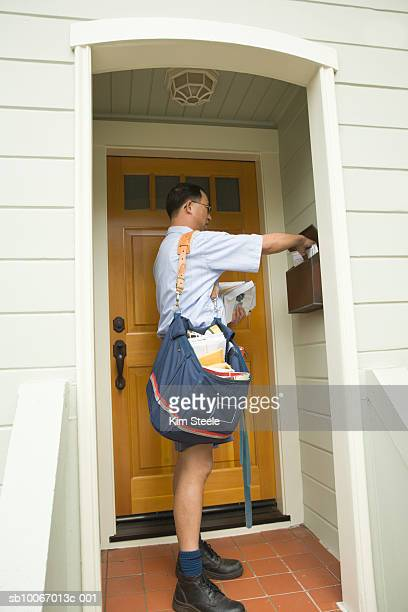 postman putting mail into mailbox by front door of house - domestic mailbox stock pictures, royalty-free photos & images