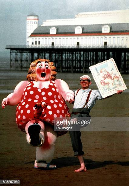 Postman rod Folkes takes a stroll down WestonSuperMare beach with a Donald McGill postcard character to launch a new set of Royal Mail stamps marking...