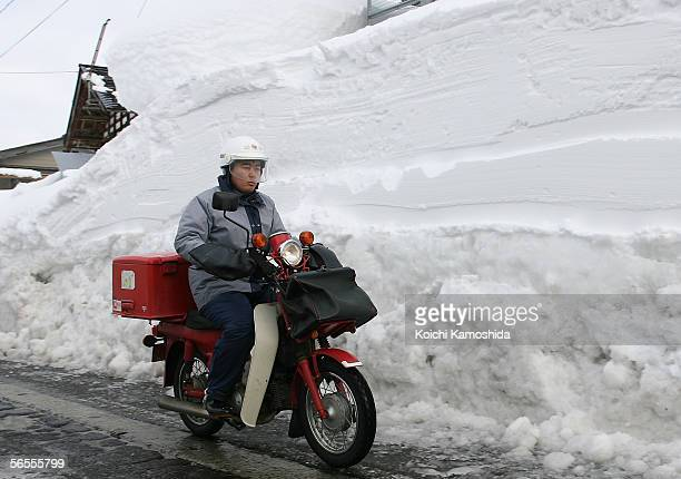 Postman runs in between the accumulated snow on January 10 2005 in Tsunanmachi Niigata Prefecture Japan The record snowfall has killed about 70...