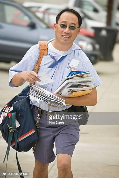 Postman walking along street with mailbag, portrait