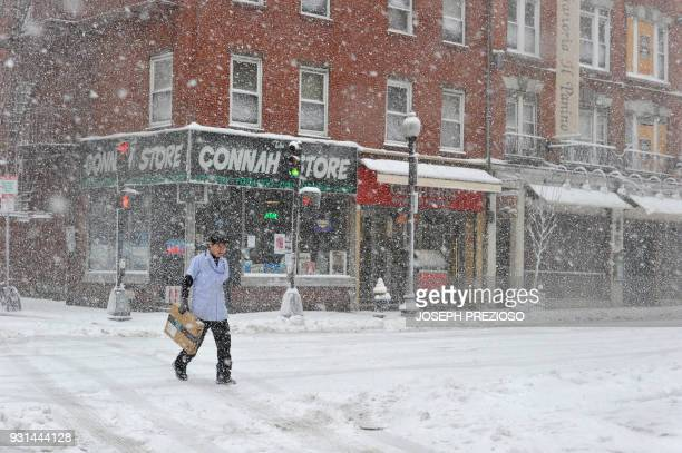 A postman walks to deliver packages in Boston's North End during a March noreaster on March 13 2018 in Boston Massachusetts / AFP PHOTO / Joseph...