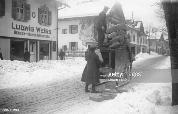 Postmitarbeiter liefern Pakete auf einem Schlitten in einer verschneiten Siedlung aus Originalaufnahme im Archiv von ullstein bild