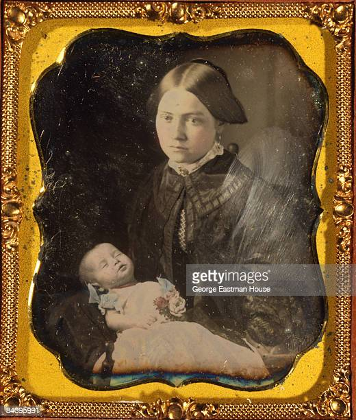 A postmortem portrait shows a woman holding her baby ca 1855 United States