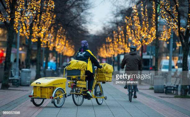 Postwoman of the Deutsche Post cycles on an E-Bike across the city centre of Hanover,Germany, 29 December 2017. Photo: Philipp Schulze/dpa