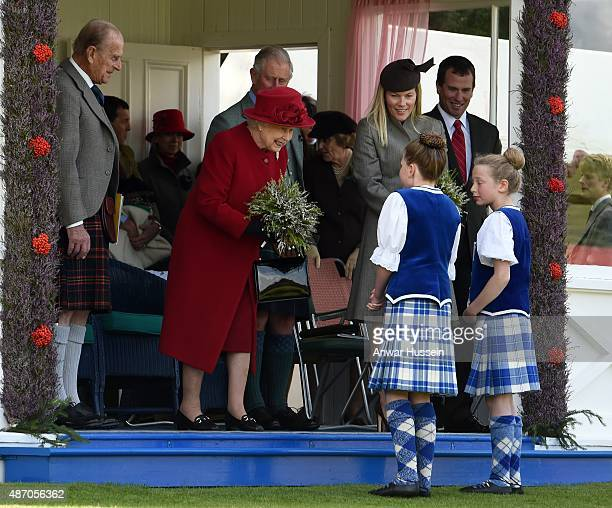 A posy of heather is presented to Queen Elizabeth ll as she attends the Breamar Highland games with Prince Philip Duke of Edinburgh Prince Charles...