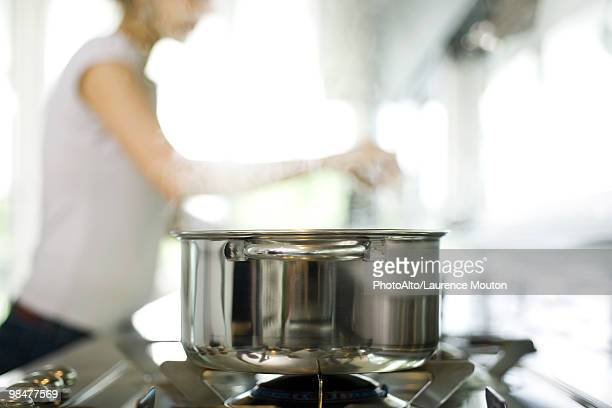 Pot cooking on stove, woman in background
