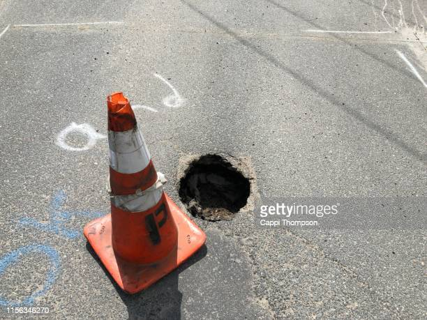 pot hole in roadway creating a hazard to motorists - sinkholes stock pictures, royalty-free photos & images
