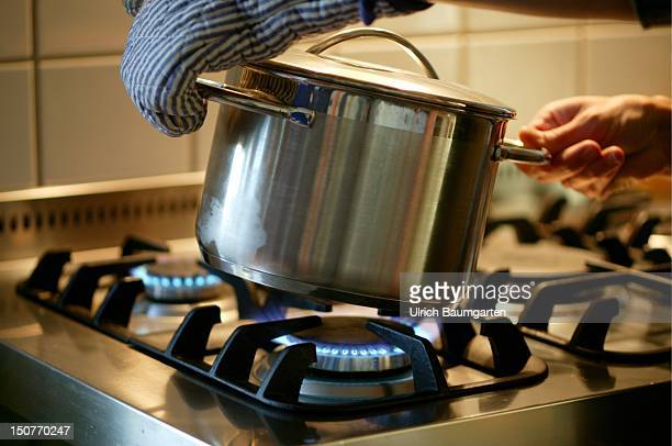 A pot is beeing taken from the gas cooker