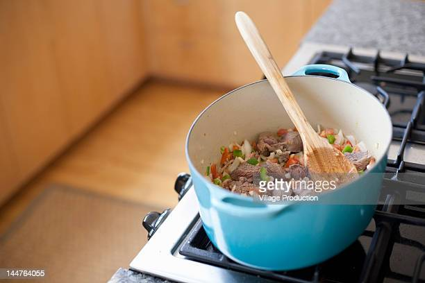 Pot of a copped vegetables and meat on a stove